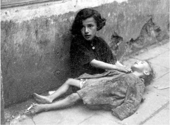Starving children sitting on the pavement in the Warsaw ghetto: Yad Vashem Photo archives.