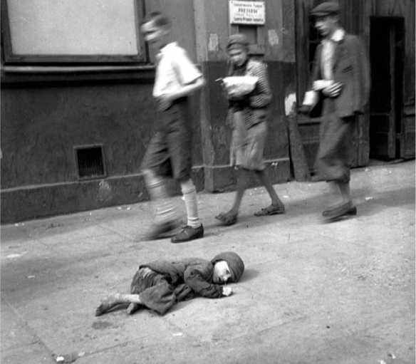 A starving child lying on the sidewalk: Warsaw Ghetto: Yad Vashem Photo archives.